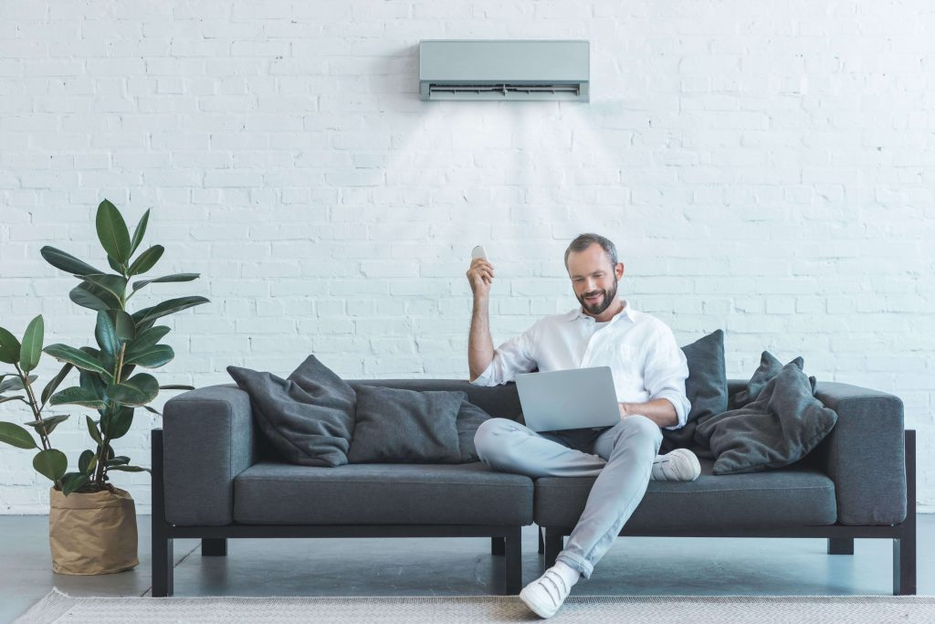 man using controller for air conditioning unit