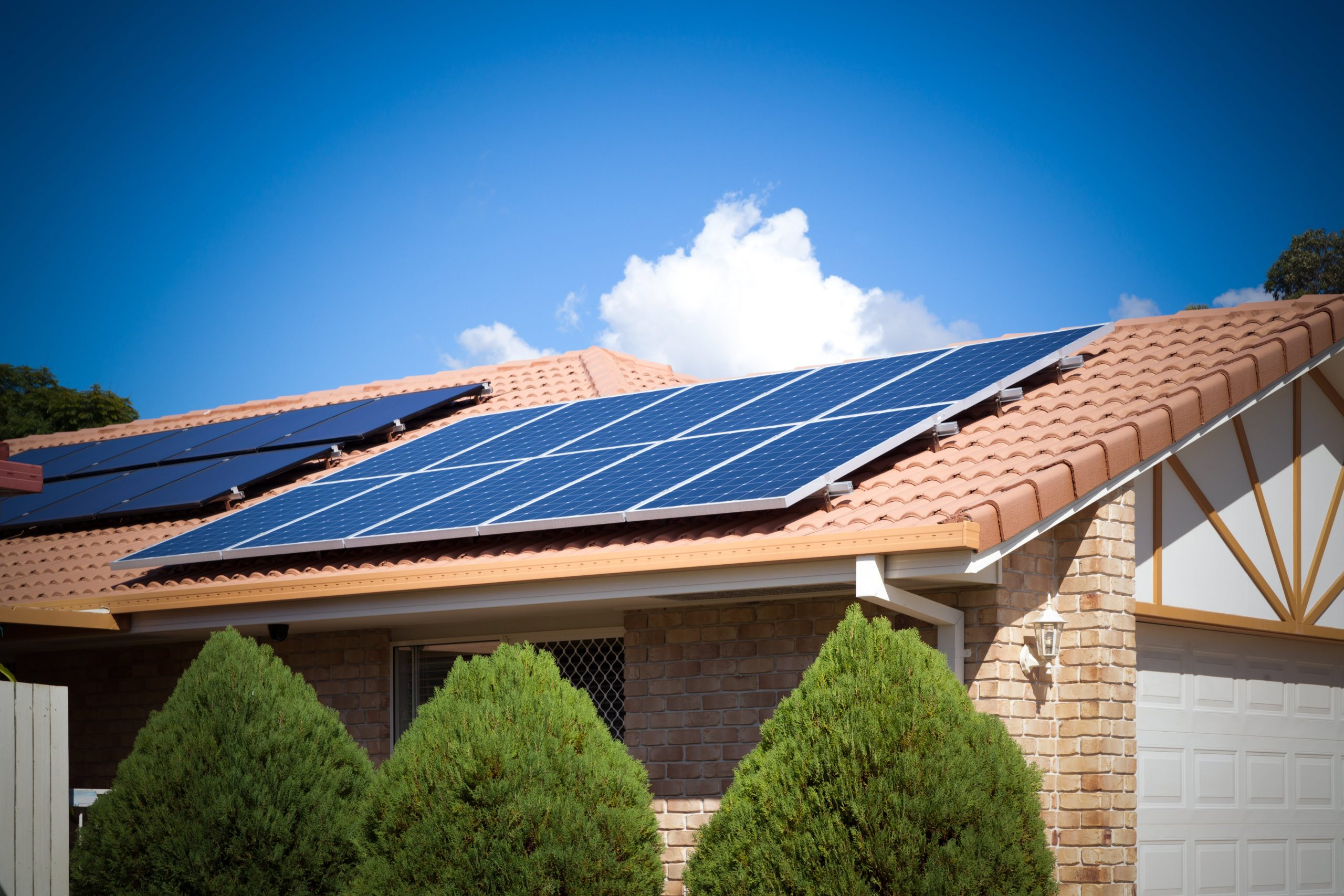 solar panels on roof with blue sky above