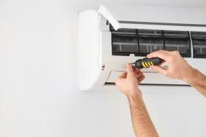 man repairing air conditioner with tools