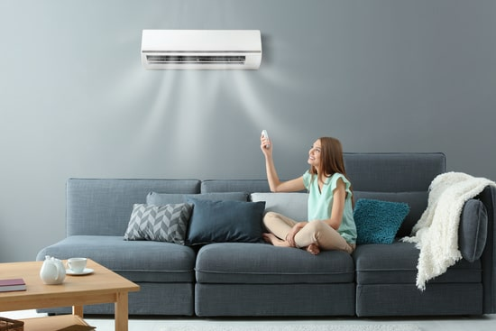 young woman using remote to control air conditioner